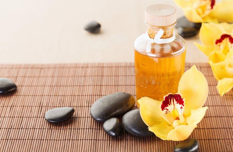Ουσιαστικό πετρέλαιο, πέτρες μασάζ και λουλούδια ορχιδεών στοκ φωτογραφίες με δικαίωμα ελεύθερης χρήσης
