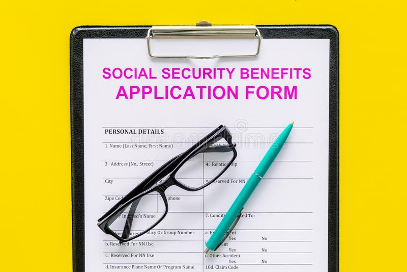 Οφέλη κοινωνικής ασφάλισης Αίτηση υποψηφιότητας κοντά στη μάνδρα και γυαλιά στην κίτρινη τοπ άποψη υποβάθρου στοκ εικόνες