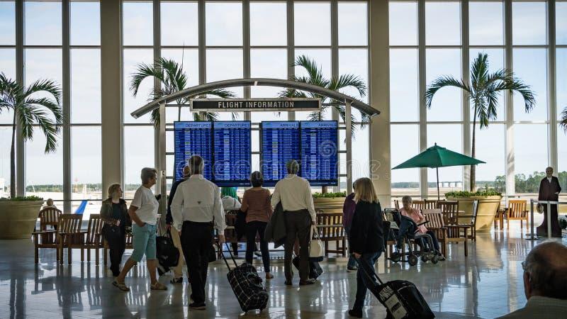 Οχυρό Meyers - Φλώριδα - 17 Δεκεμβρίου 2017 - οι επιβάτες ελέγχω έξω τα informations πτήσης στο νοτιοδυτικό διεθνή αερολιμένα κατ στοκ εικόνα