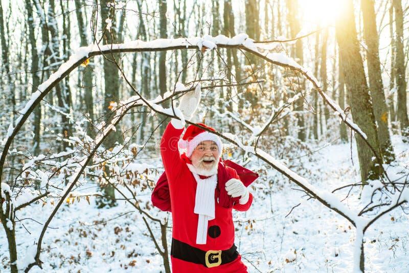 Ο Άγιος Βασίλης έρχεται στο χειμερινό δάσος με μια τσάντα με δώρα στο χιόνι Άγιος Βασίλης με μεγάλη τσάντα Ψυχρός Δεκέμβριος στοκ φωτογραφία με δικαίωμα ελεύθερης χρήσης