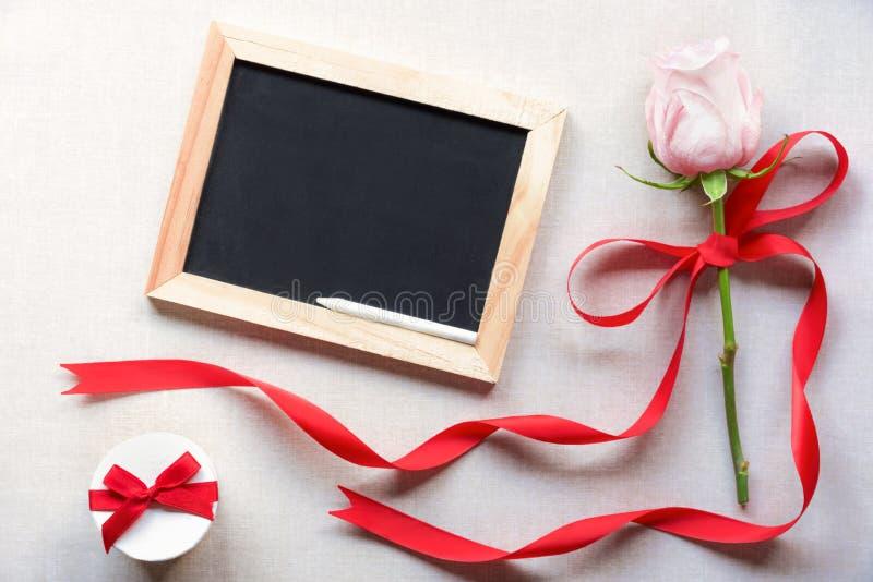 Ο άγραφος πίνακας και αυξήθηκε με την κόκκινη κορδέλλα στοκ εικόνα
