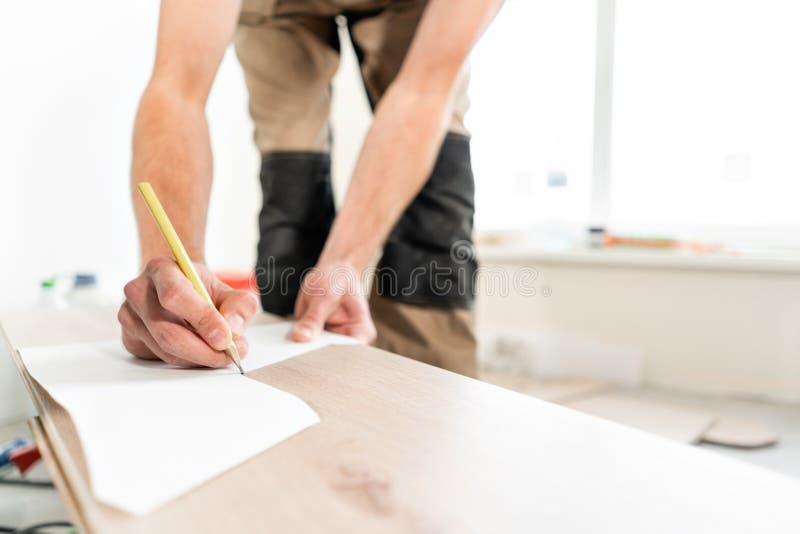 Ο άνδρας εργαζόμενος εφαρμόζει τα σημάδια στην επιτροπή για την κοπή με ένα πριόνι electrofret εγκατάσταση του νέου ξύλινου φυλλό στοκ φωτογραφία