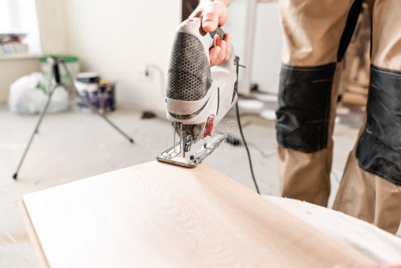 Ο άνδρας εργαζόμενος κόβει το φυλλόμορφο πίνακα με ένα πριόνι electrofret εγκατάσταση του νέου ξύλινου φυλλόμορφου δαπέδου Έννοια στοκ εικόνα