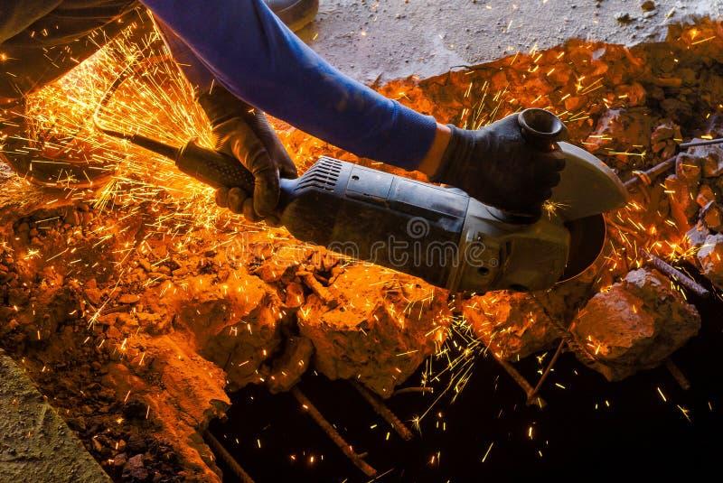 Ο άνδρας εργαζόμενος πριονίζει αλέθοντας armature πριονιών δίσκων σε μια ενισχυμένη συγκεκριμένη επιτροπή, η καταστροφή του παλαι στοκ φωτογραφία με δικαίωμα ελεύθερης χρήσης
