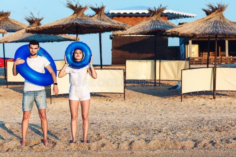 Ο άνδρας και η γυναίκα θέτουν στην παραλία και κρατούν τους διογκώσιμους κύκλους έννοια των διακοπών θερινής θάλασσας στοκ εικόνα με δικαίωμα ελεύθερης χρήσης
