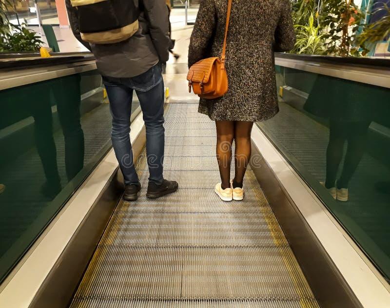 Ο άνδρας και η γυναίκα κατεβαίνουν την κυλιόμενη σκάλα στη λεωφόρο αγορών Πόδια, παπούτσια, σακίδιο πλάτης, πορτοφόλι υποστηρίξτε στοκ εικόνα με δικαίωμα ελεύθερης χρήσης