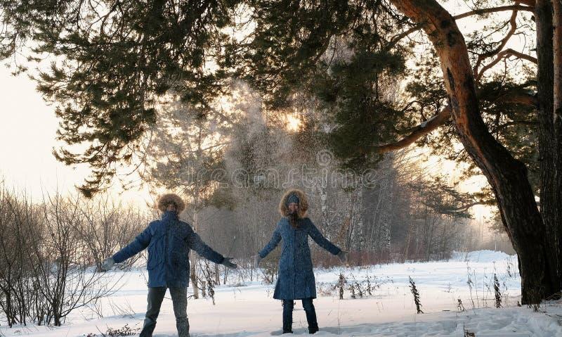 Ο άνδρας και μια γυναίκα στα μπλε κάτω σακάκια ρίχνουν το χιόνι επάνω στο χειμερινά δάσος και το χαμόγελο Μπροστινή όψη στοκ εικόνα