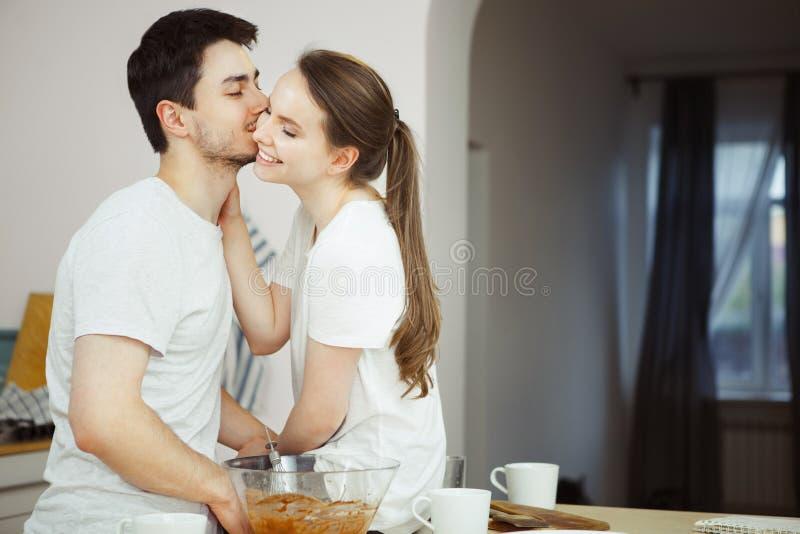 Ο άνδρας με τις ιδιαίτερες προσοχές φιλά tenderly τη γυναίκα στο μάγουλο στην κουζίνα στοκ εικόνες