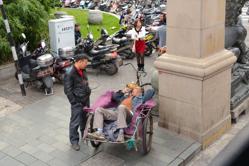Ο άνθρωπος αναπαύεται σε τρίτροχα ταξί στη Σαγκάη της Κίνας στοκ φωτογραφία