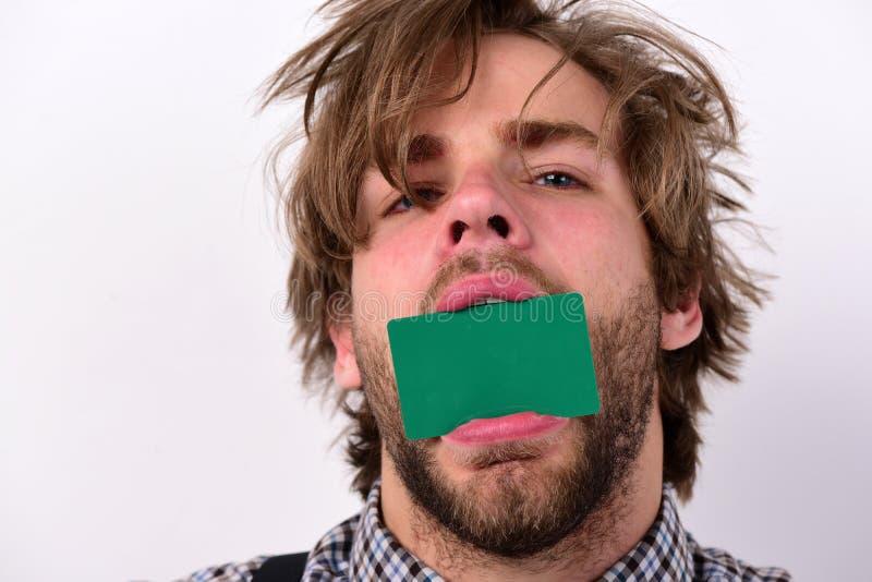 Ο άνθρωπος κρατά σκούρα πράσινη κάρτα στο στόμα στοκ εικόνες