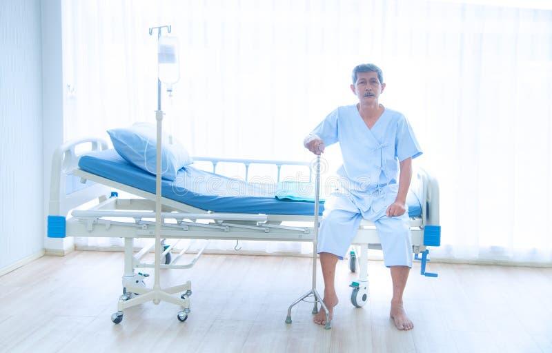 Ο άρρωστος ή ηλικιωμένος Ασιάτης γέρος που κάθεται μόνος στο κρεβάτι του ασθενούς με ένα μπαστούνι που περιμένει το γιατρό στοκ φωτογραφία