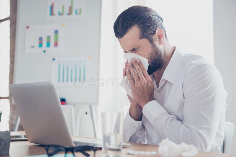 Ο άρρωστος επιχειρηματίας με τις εργασίες θερμοκρασίας στην αρχή και σκουπίζει δικούς του στοκ φωτογραφία με δικαίωμα ελεύθερης χρήσης