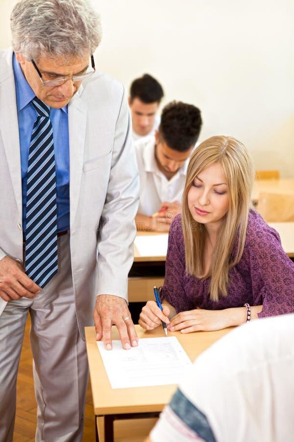 Ο δάσκαλος παρατηρεί τους σπουδαστές του στοκ φωτογραφία με δικαίωμα ελεύθερης χρήσης