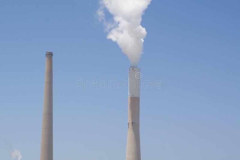 Ο άσπρος καπνός αυξάνεται από το ριγωτό σωλήνα στον μπλε ασυννέφιαστο ουρανό μια φωτεινή, ηλιόλουστη ημέρα Άνθρακας και με γκάζι  στοκ φωτογραφία