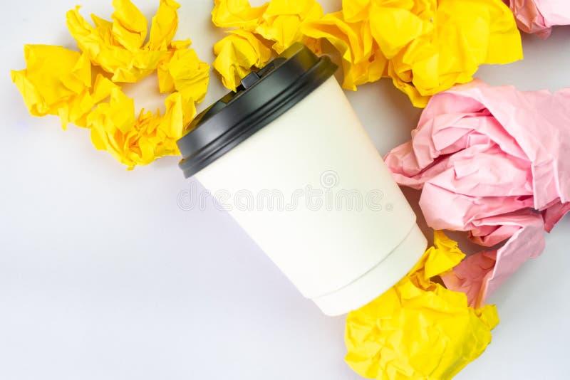 Ο άσπρος καφές παίρνει μαζί το φλυτζάνι με τις ζωηρόχρωμες θρυμματισμένες σφαίρες εγγράφου στο άσπρο υπόβαθρο στοκ εικόνα με δικαίωμα ελεύθερης χρήσης