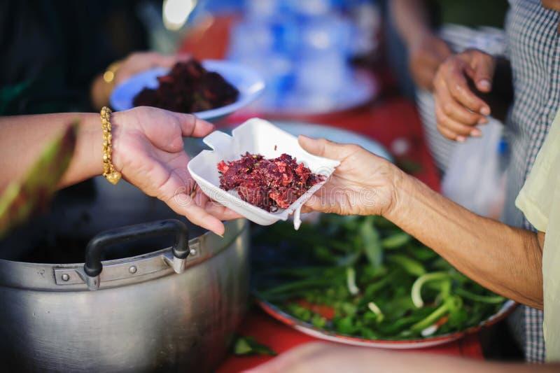 Ο άστεγος παίρνει τα τρόφιμα φιλανθρωπίας από τους χορηγούς τροφίμων στην κοινωνία: Η έννοια του προβλήματος επαιτών στη γη: Το χ στοκ εικόνα
