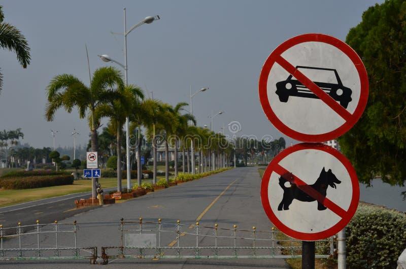 Ο άσχημος κύκλος κανένα αυτοκίνητο και κανένα σκυλί υπογράφει μπροστά από το δρόμο στο πάρκο στοκ εικόνες