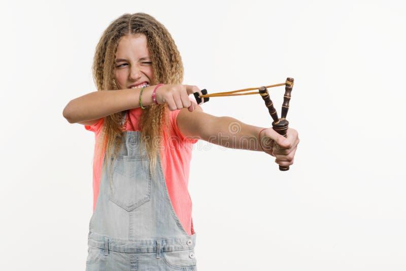 Ο άτακτος έφηβος κοριτσιών με τη σγουρή τρίχα κρατά μια σφεντόνα Άσπρο στούντιο υποβάθρου στοκ φωτογραφία με δικαίωμα ελεύθερης χρήσης