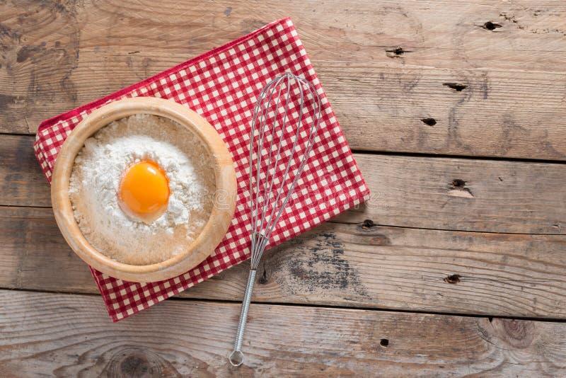 Ο λέκιθος αυγών στο αλεύρι και κτυπά για την ήττα στον ξύλινο πίνακα κορυφή VI στοκ φωτογραφία