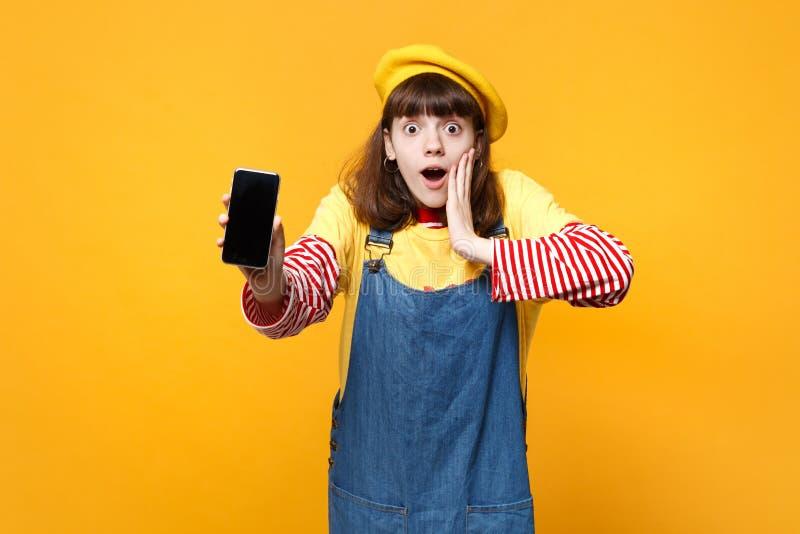 Ο έκπληκτος έφηβος κοριτσιών γαλλικό beret έβαλε το χέρι στο πρόσωπο που κρατά το κινητό τηλέφωνο με την κενή κενή οθόνη που απομ στοκ φωτογραφία