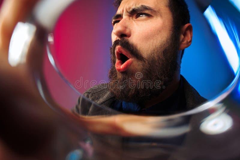 Ο έκπληκτος νεαρός άνδρας στο κόμμα ντύνει την τοποθέτηση με το ποτήρι του κρασιού στοκ εικόνες με δικαίωμα ελεύθερης χρήσης