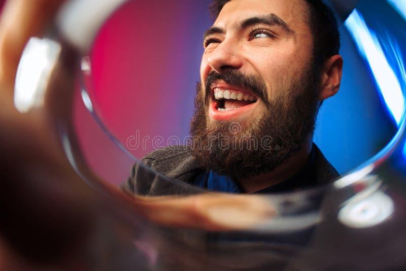 Ο έκπληκτος νεαρός άνδρας στο κόμμα ντύνει την τοποθέτηση με το ποτήρι του κρασιού στοκ φωτογραφίες