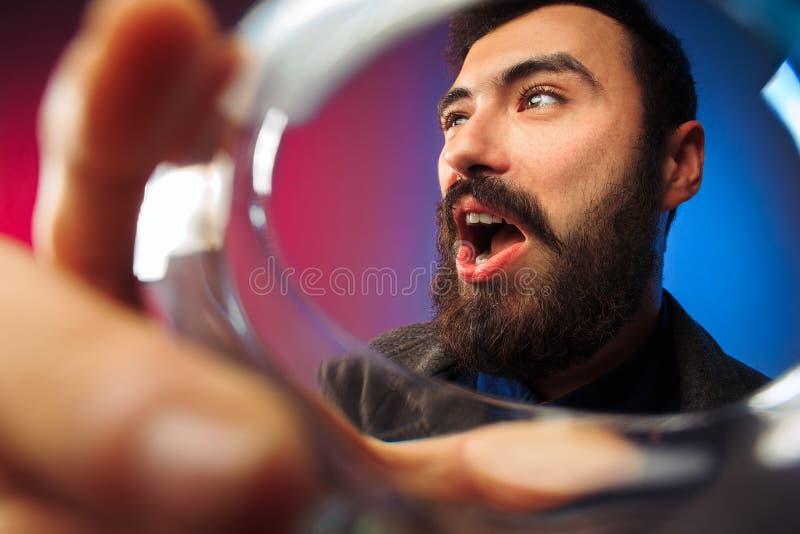 Ο έκπληκτος νεαρός άνδρας στο κόμμα ντύνει την τοποθέτηση με το ποτήρι του κρασιού στοκ εικόνες