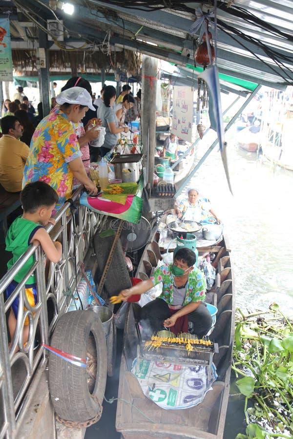 Ο έμπορος ψήνει το χοιρινό κρέας στη βάρκα που εξυπηρετεί στους πελάτες στοκ φωτογραφίες με δικαίωμα ελεύθερης χρήσης