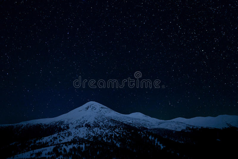 Ο έναστρος ουρανός επάνω από τις χιονώδεις αιχμές των βουνών στοκ εικόνες