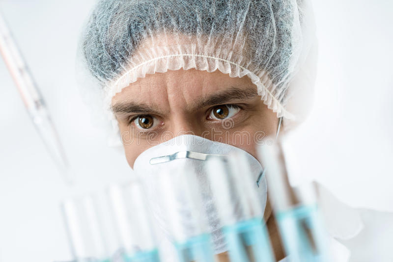 Ο έντονος επιστήμονας με τα καφετιά μάτια στην προστατευτική ένδυση φορτώνει τα δείγματα στοκ φωτογραφία με δικαίωμα ελεύθερης χρήσης