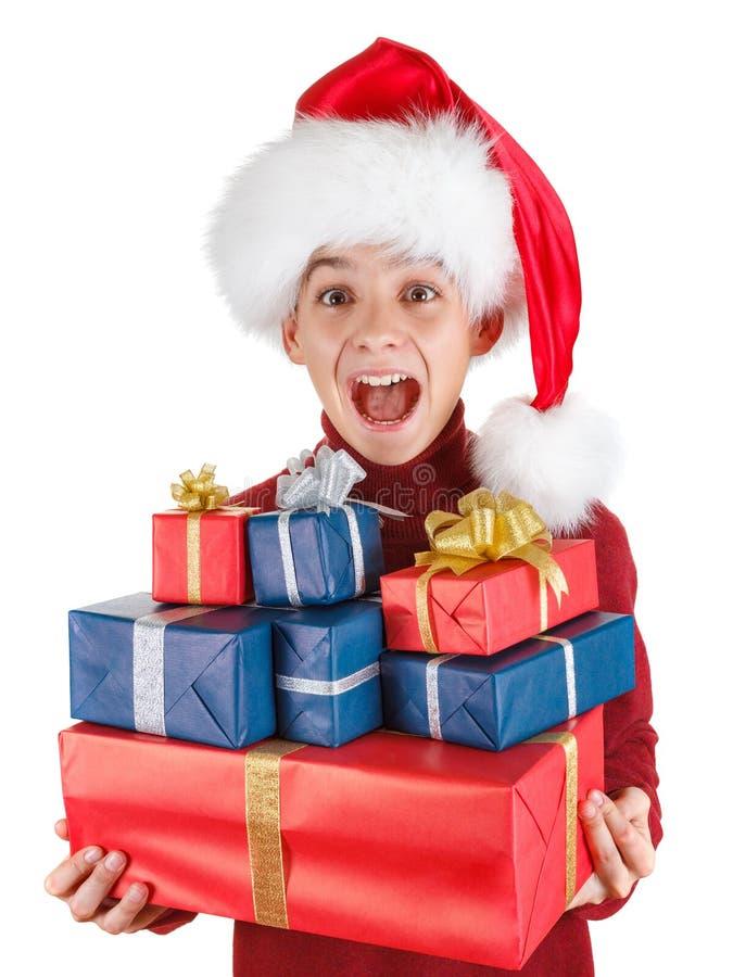 Ο έφηβος αγοριών στο καπέλο santa είναι ευτυχή δώρα για τα Χριστούγεννα, νέο έτος στοκ εικόνα με δικαίωμα ελεύθερης χρήσης