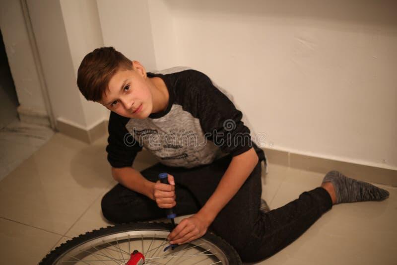 Ο έφηβος επισκευάζει το ποδήλατο στοκ εικόνα με δικαίωμα ελεύθερης χρήσης