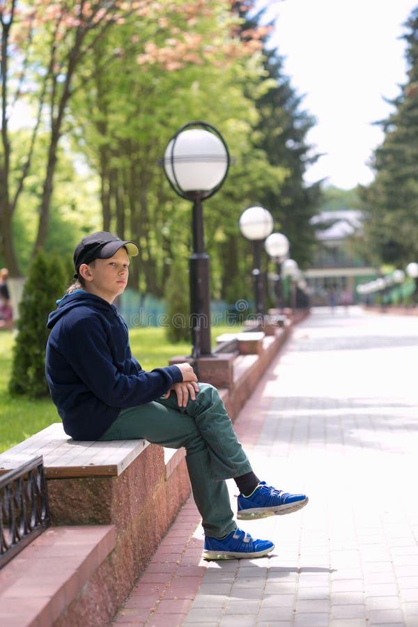 Ο έφηβος κάθεται σε έναν πάγκο σε ένα θερινό πάρκο στοκ φωτογραφία με δικαίωμα ελεύθερης χρήσης