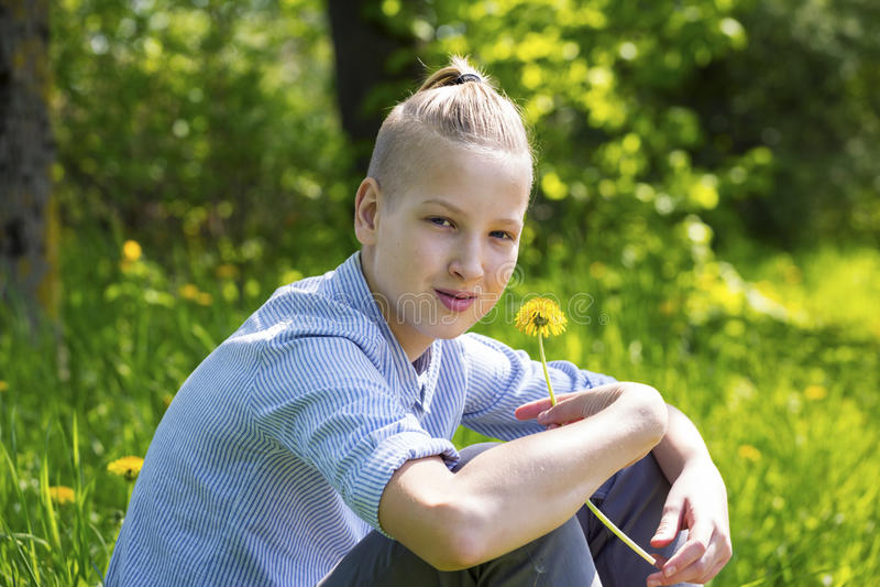 Ο έφηβος κάθεται στη χλόη στοκ φωτογραφίες