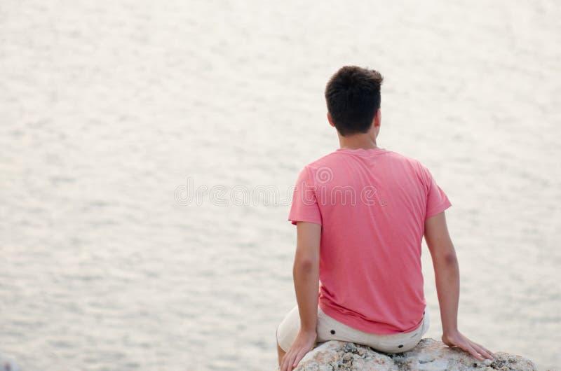 Ο έφηβος μελαγχολικός κάθεται με την πλάτη πάνω από τη μεγάλη πέτρα α στοκ φωτογραφίες