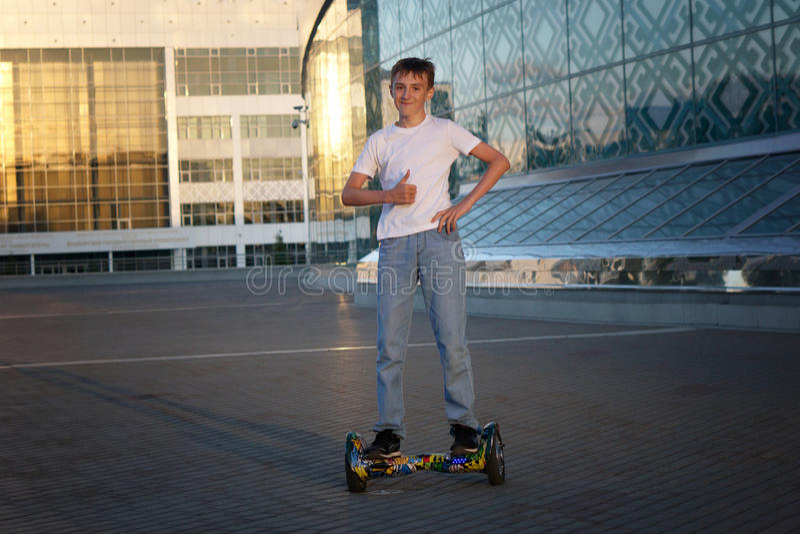 Ο έφηβος οδηγά σε ένα ηλεκτρικό μηχανικό δίκυκλο, με ένα χαμόγελο και θετικές συγκινήσεις στοκ εικόνες