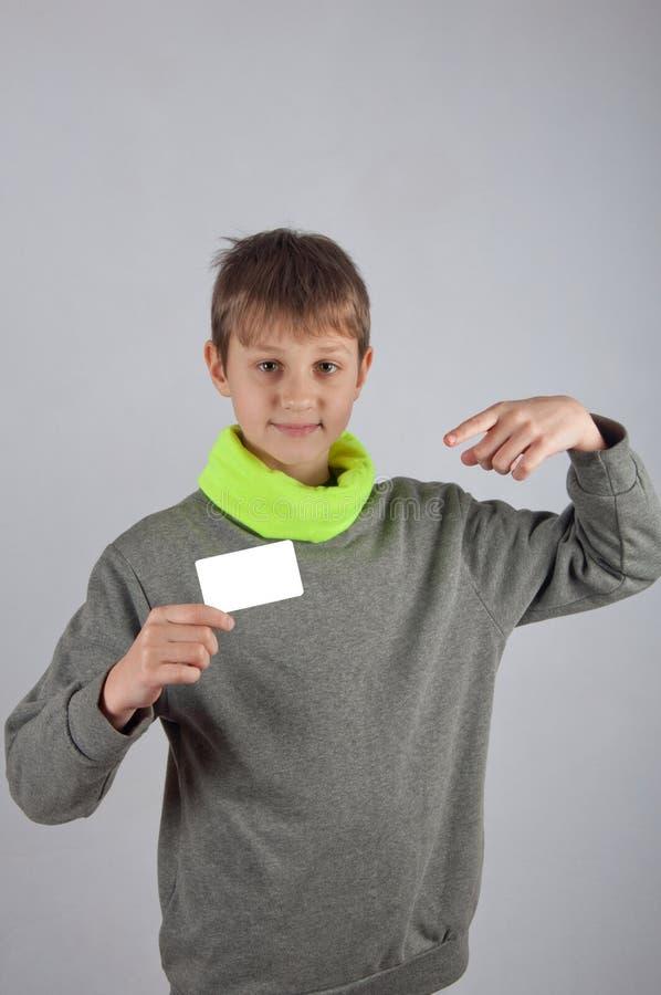 Ο έφηβος στην γκρίζα, πράσινη εκμετάλλευση πουλόβερ whte λαναρίζει και poiting επάνω σε το με το δάχτυλο στοκ φωτογραφία