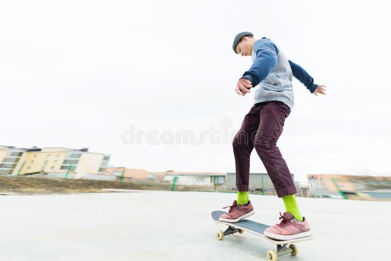Ο έφηβος skateboarder οδηγά το skatepark στο νεφελώδη καιρό Αστικός πολιτισμός νεολαίας στοκ εικόνες