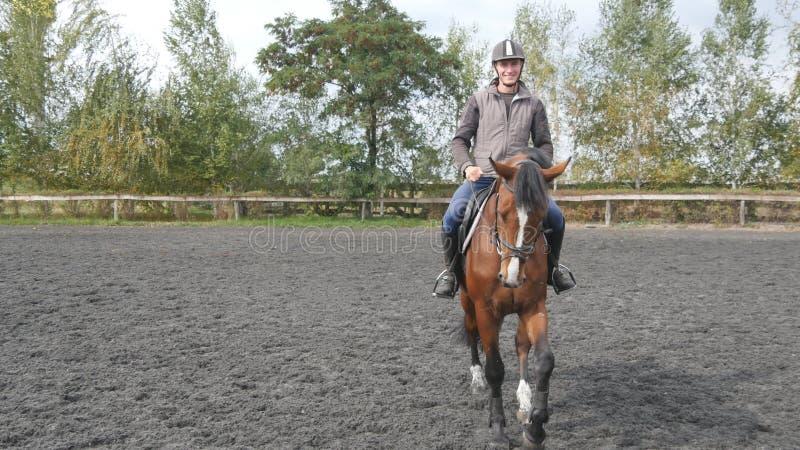 Οδήγηση πλατών αλόγου νεαρών άνδρων υπαίθρια Αρσενικό jockey στο άλογο που περπατά στο manege στο αγρόκτημα τη σκοτεινή νεφελώδη  στοκ εικόνες