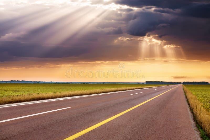 Οδήγηση στην κενή εθνική οδό προς τις ηλιαχτίδες στοκ φωτογραφία