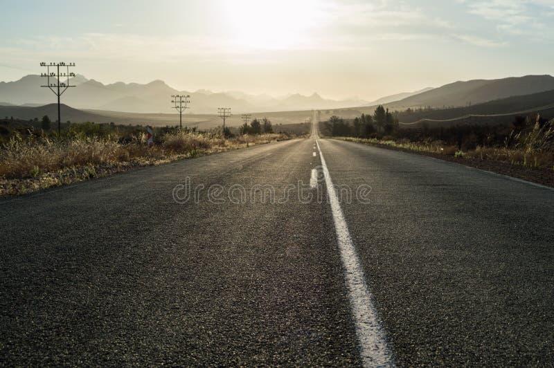 Οδήγηση στο ηλιοβασίλεμα σε μια εθνική οδό σε ένα τοπίο βουνών στοκ εικόνες με δικαίωμα ελεύθερης χρήσης