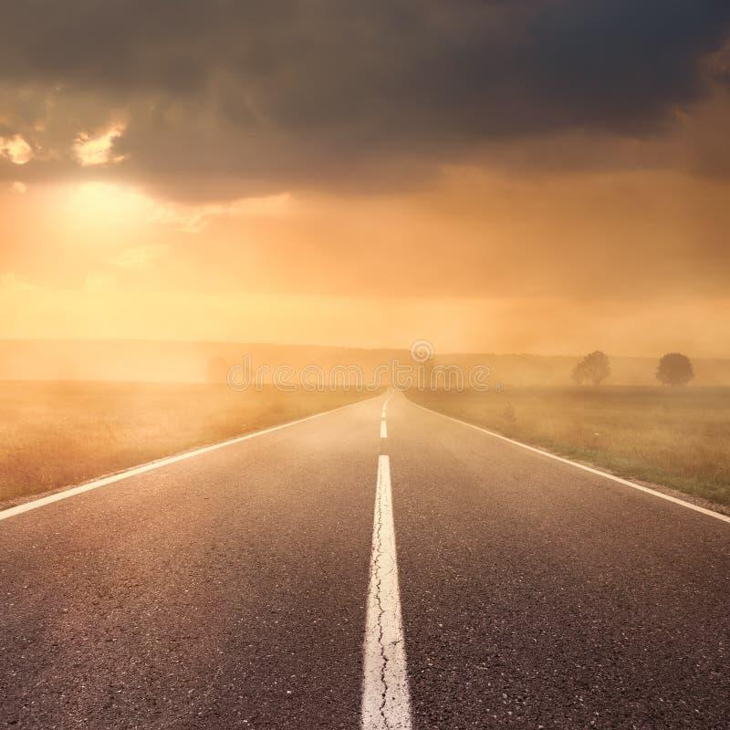 Οδήγηση στο δρόμο ασφάλτου στο ηλιοβασίλεμα προς τον ήλιο ΙΙ στοκ φωτογραφία