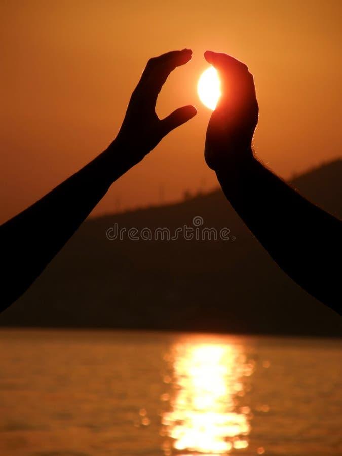 ο ήλιος ανδρών χεριών παίρν&epsil στοκ εικόνες