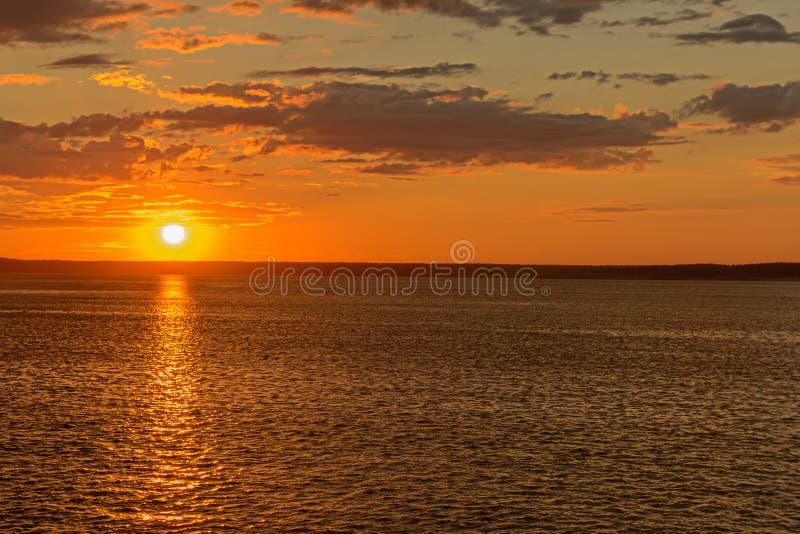 ο ήλιος κατεβαίνει τον ορίζοντα επάνω από τον ποταμό στοκ εικόνα