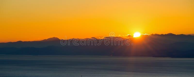 Ο ήλιος που θέτει πίσω από τα βουνά στα σύννεφα πέρα από την ακτή και την πόλη στοκ φωτογραφία