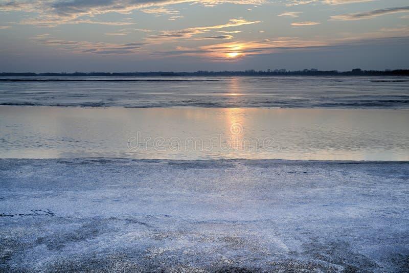 Ο ήλιος που τίθεται πέρα από την παγωμένη λίμνη στοκ φωτογραφίες με δικαίωμα ελεύθερης χρήσης