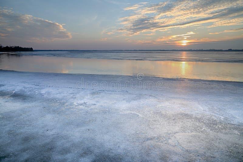 Ο ήλιος που τίθεται πέρα από την παγωμένη λίμνη στοκ εικόνα με δικαίωμα ελεύθερης χρήσης