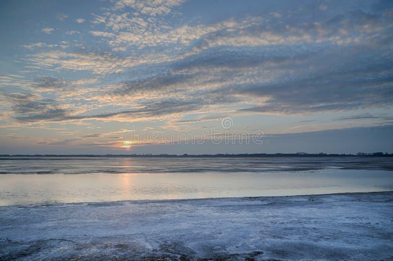 Ο ήλιος που τίθεται πέρα από την παγωμένη λίμνη στοκ εικόνες
