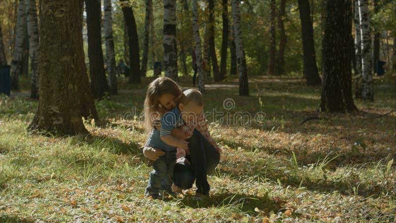 Ο αγαπώντας γιος φέρνει smth στην ευτυχή μητέρα του και την αγκαλιάζει στο πάρκο στοκ φωτογραφίες