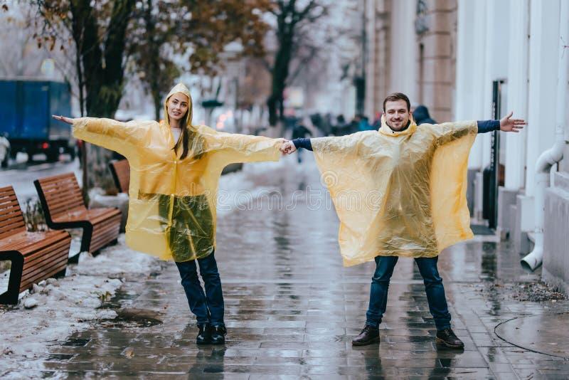 Ο αγαπώντας τύπος και το κορίτσι έντυσαν στην κίτρινη στάση αδιάβροχων στην οδό στη βροχή στοκ εικόνες